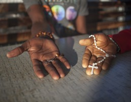 Zang and DHL from Cameroon and residents at the Moria camp in Lesbos are showing their crucifix as a symbol of their faith.