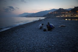 Iranian refugees are breaking their fast during Ramadan on the beach in Ventimiglia, Italy. In the distance is France. July 2015.